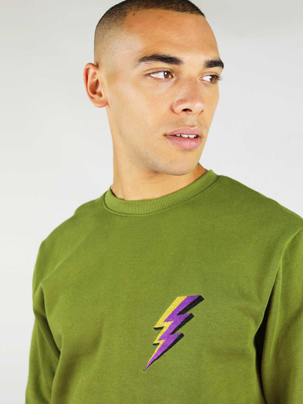 The thunder organic sweatshirt in green has a thunder embroidery on the chest in purple and yellow and crew neck. Slightly oversized fit for extra comfort.