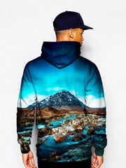 Model in pullover hoodie with blue sky, mountain and flowing river all over print