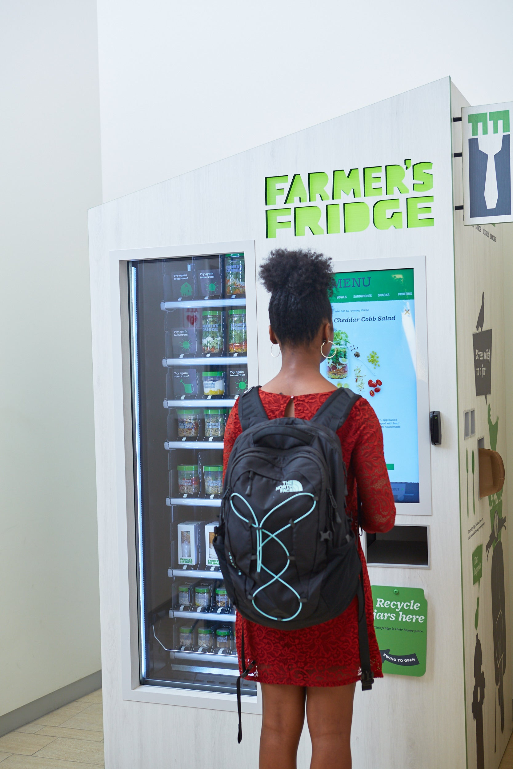 Student wearing black North Face backpack is placing an order at a Farmer's Fridge vending kiosk.