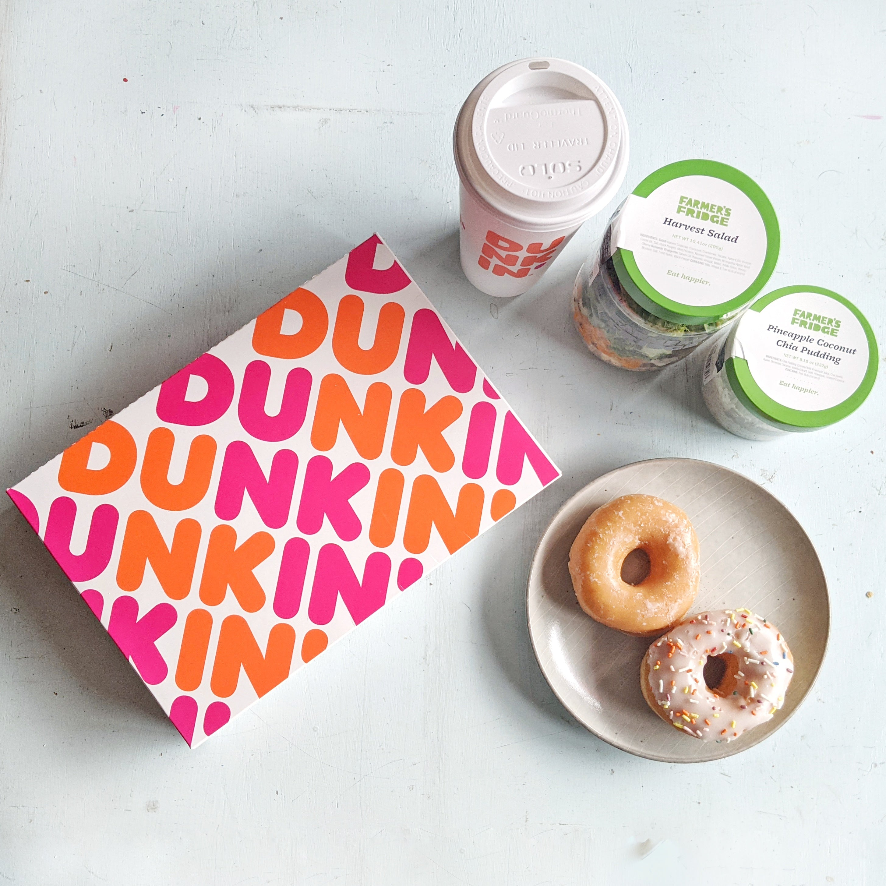 From left to right: Pink and orange Dunkin' Donuts box, a Dunkin Donut's coffee cup, two Farmer's Fridge jars. Below the jar is a small, round plate with two doughnuts on it.