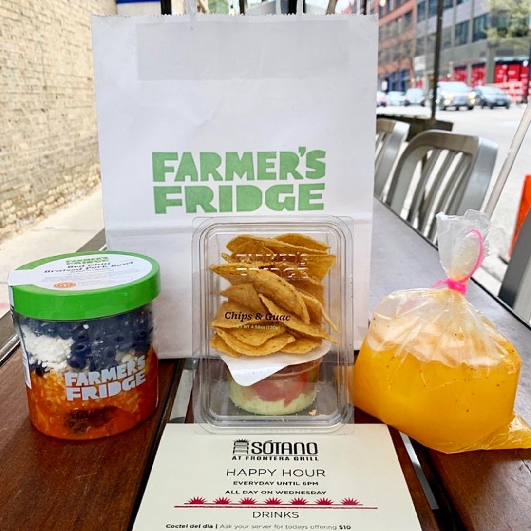 Meal kit on top of a wooden patio table. From left to right is a Red Chile Braised Pork Bowl in a Farmer's Fridge jar; A white takeout bag with a green Farmer's Fridge logo; Chips and Guac snack; orange mocktail drink in a plastic bag.
