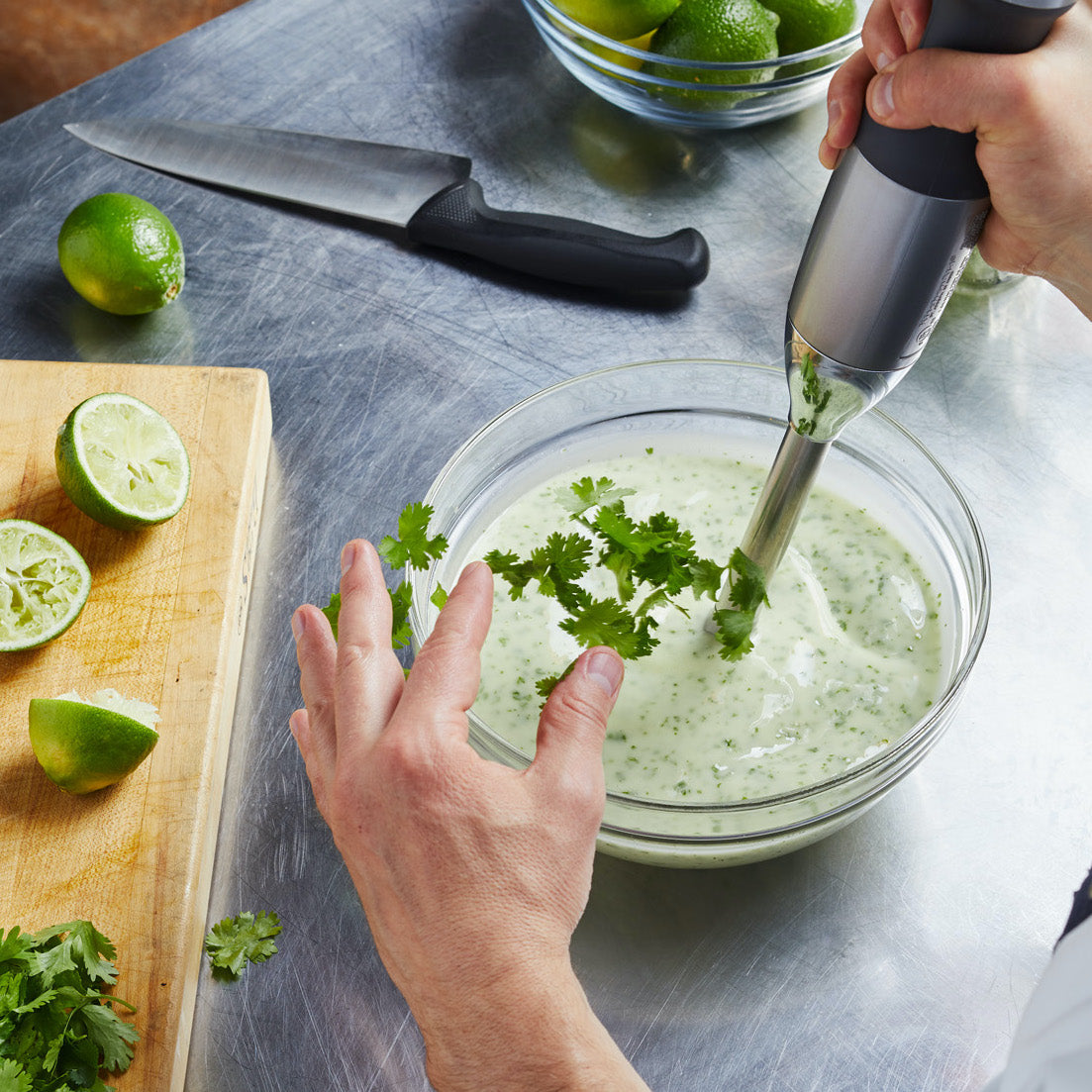 On top of a stainless steel kitchen work station sits a wood chopping board with three lime halves and cilantro leaves. Beside the board is a clear mixing bowl filled with a green sauce being spun by hand blender.