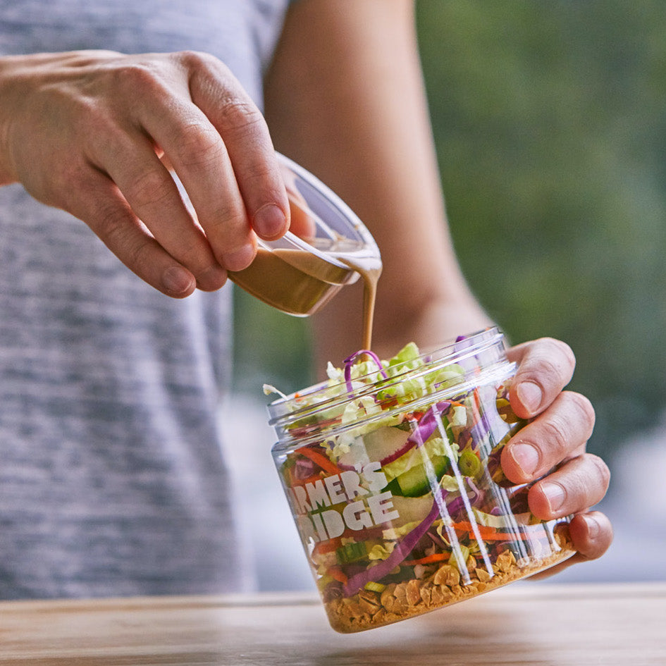 Hand is pouring a brown balsamic vinaigrette dressing into a jar of salad over a brown table.
