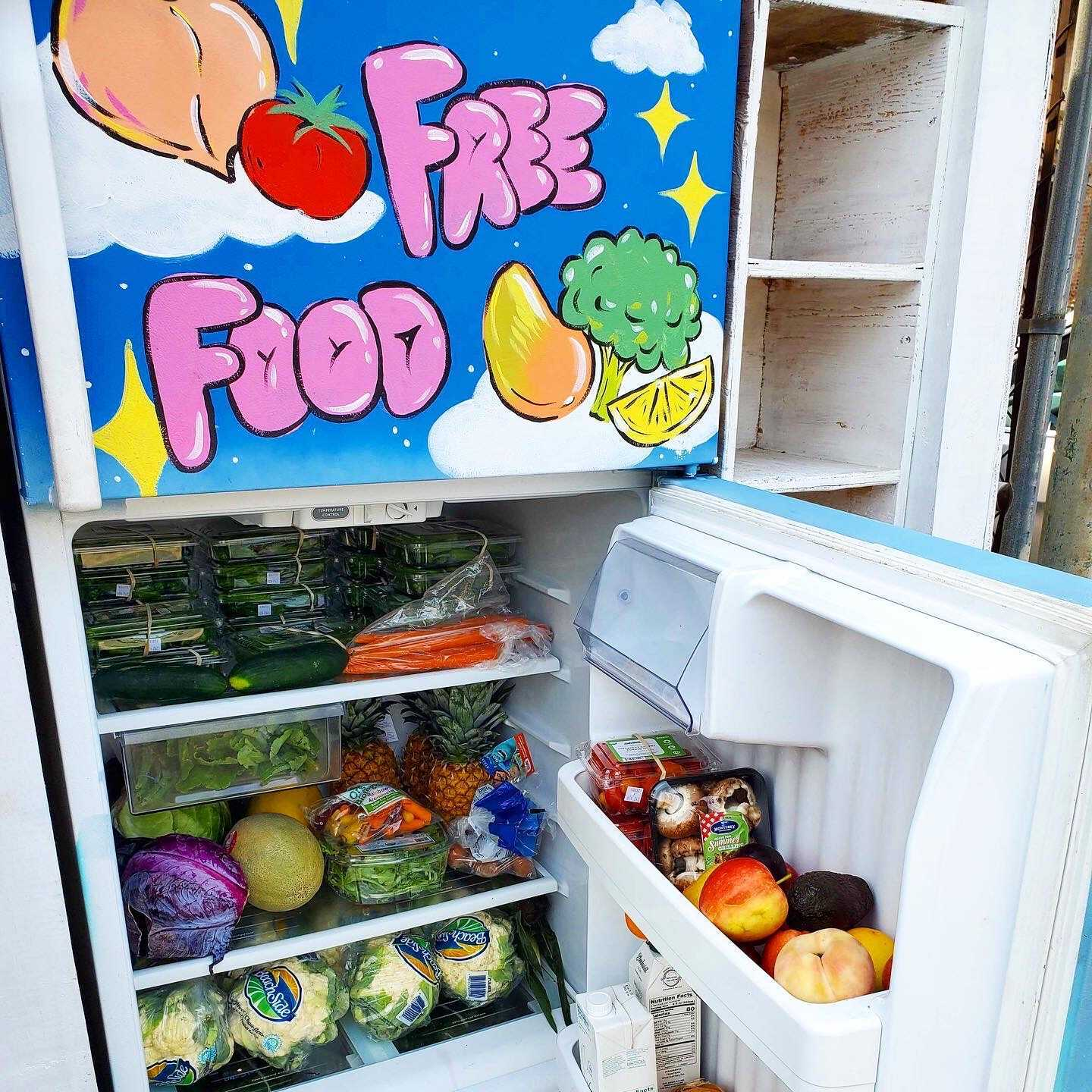 "Dirt Farms Fridge in Chicago's Humboldt Park neighborhood. ""Free Food"" is painted on the front and the fridge is stocked with fresh produce."