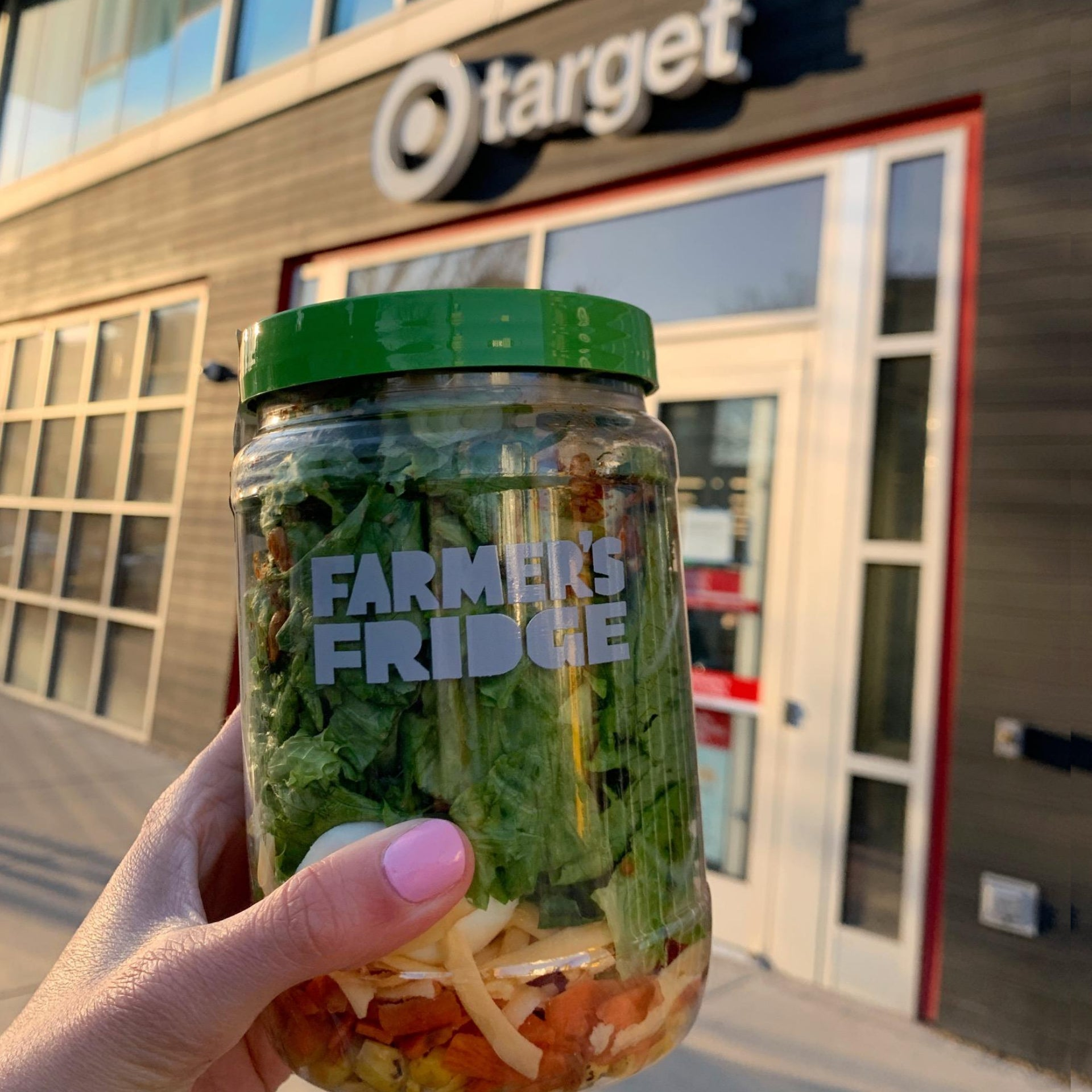 Hand holding a Farmer's Fridge salad jar in front of a Target store.