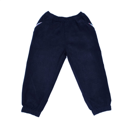 Front view of the Akbar trousers. Midnight blue corduroy with two slit pockets. Elasticated ankles.