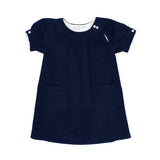 Front view of the Henriette dress. Midnight blue corduroy. Two-buttons closing at the neck. Shirt sleeves with button.