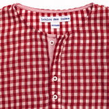 Detail view of the button placket of the Lysandre kurta in red gingham. Lining in contrasting fabric with red micro checks.