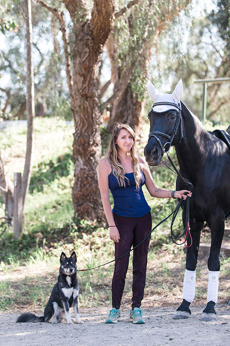 Founder holding her alaskan klee kai and a black horse