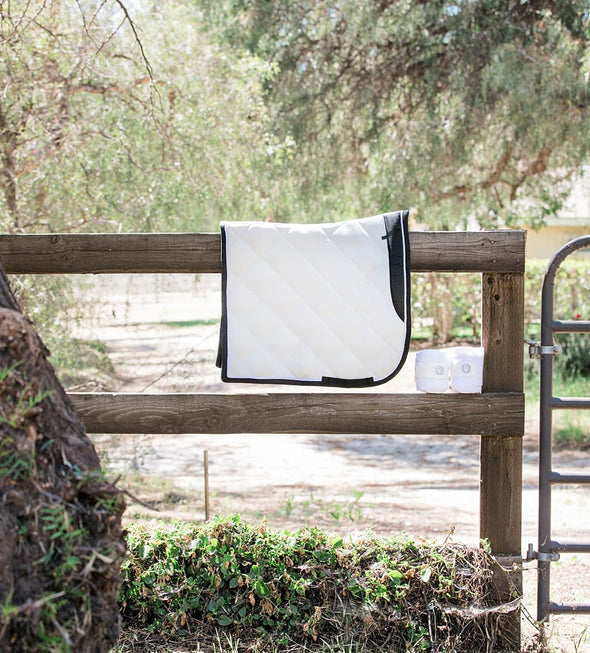 White Dressage saddle pad and polo wraps on a natural wood fence. Trees are in the background. White Dressage Bundle with Fly Veil, Polo Wraps and a Dressage saddle pad. White in color with semi shiny material.