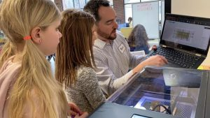 Students operates FLUX laser cutter