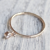 gold ring with a dangle gemstone charm