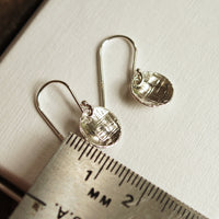 silver disc earrings with ruler for size