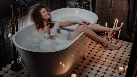 woman in bathtub with candles and glass of wine