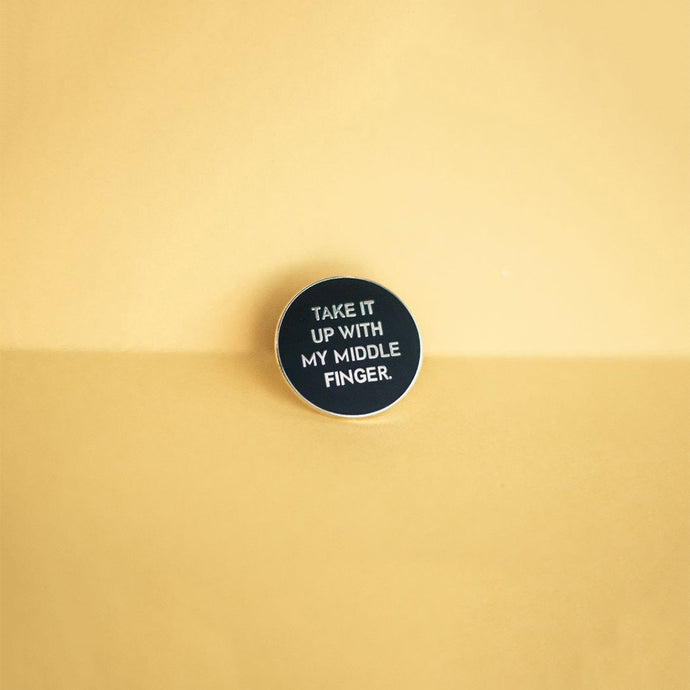 Cute pins that are filled with sass! Round, black enamel pin that says 'Take It Up With My Middle Finger.'