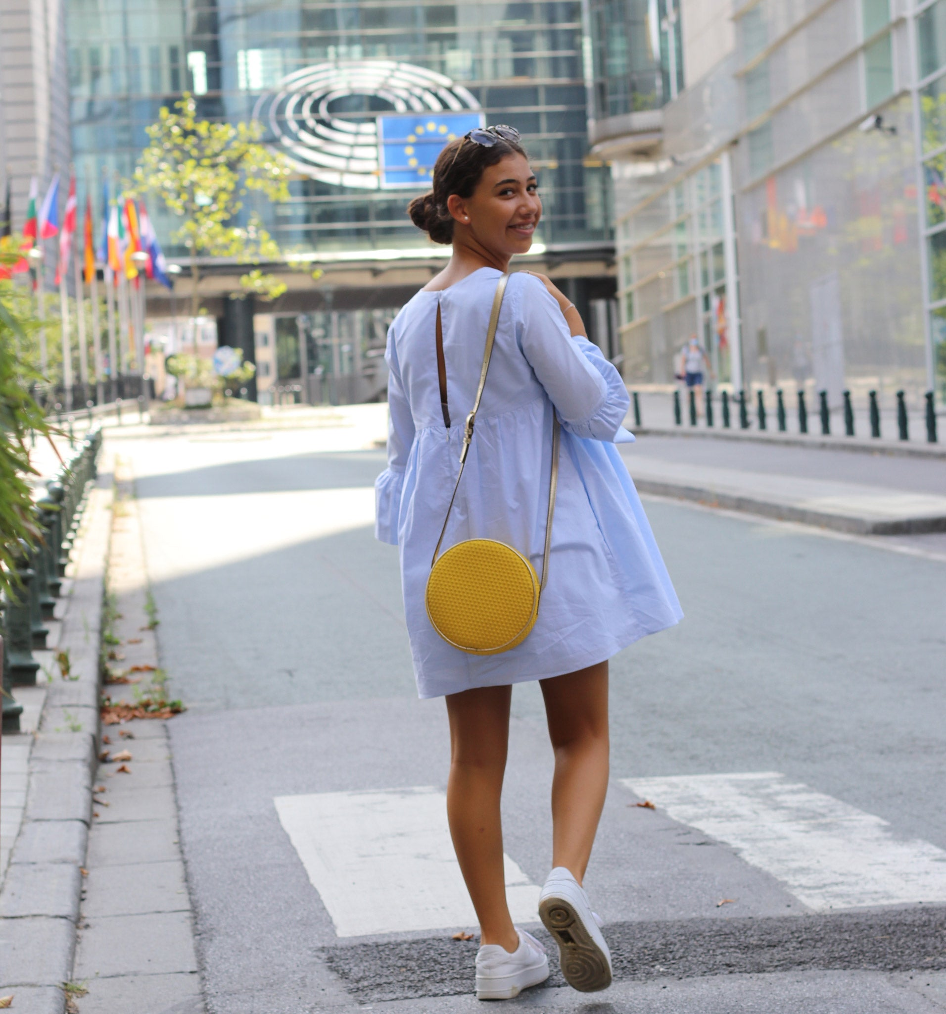 Bags-by-Sumageza-SU-young-lady-walking-into the EU-Parliament-building-dressed-in-a-light-blue-summer-dress-and-wearing-the-shoulder-bag-boite-de-chocolat-neo-in-bright-yellow-color