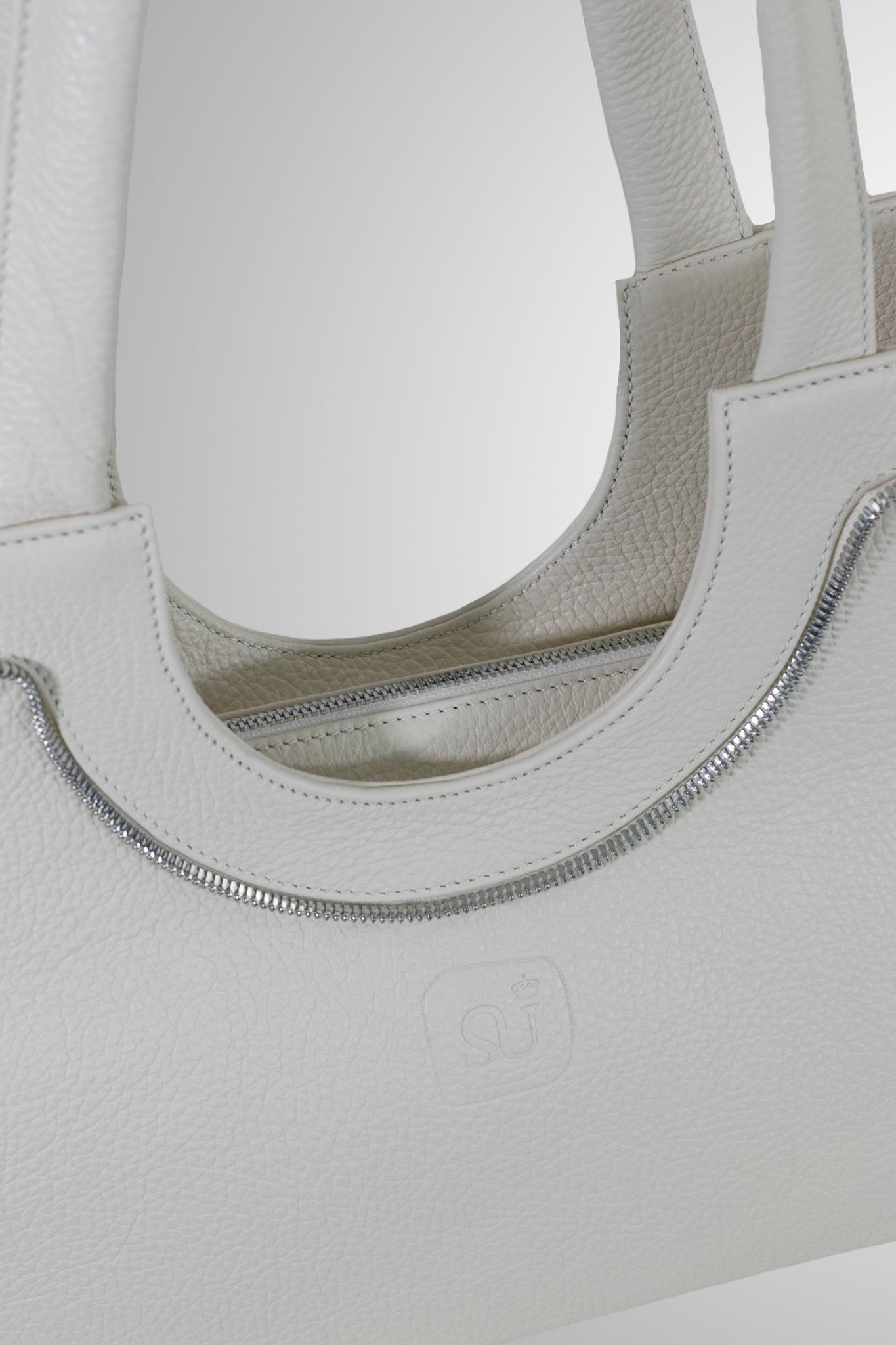 Bags-by-Sumageza-Shoulderbag-Le-Zip-comfortable-shoulder-bag-in-light-beige-calf-leather-detail-of-bag-front-shown-with-zip-transformed-into-and-used-as-decor-element