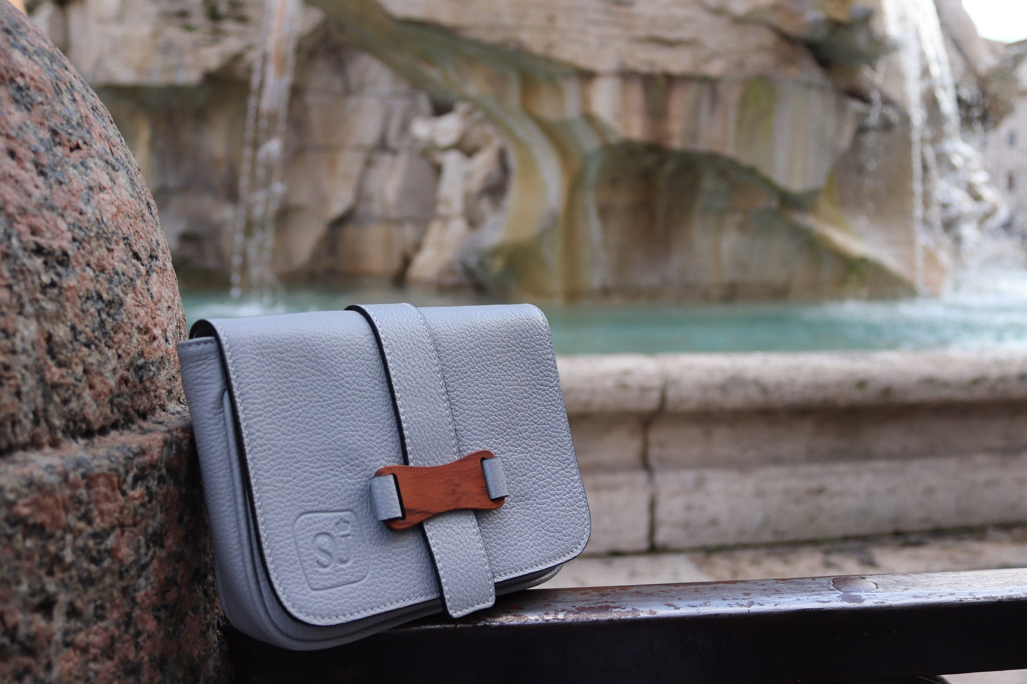Bags-by-Sumageza-Su-light-grey-crossbody-bag-made of-calf-leather-shown-on-rim-of-famous-fountain-in-Rome-Italy