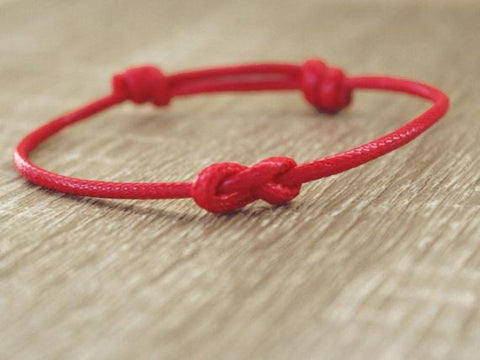 """In Christianity, Genesis: 38 mentions the red string to """"worn off misfortunes"""". It is also generally worn on the left wrist. In Christianity, red is a symbol of fire, blood, and Pentecost. It also became the color of the martyred saints."""