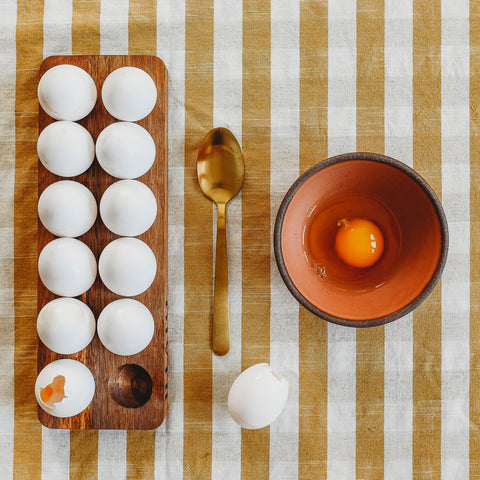 A wooden tray of eggs and a bowl with a raw egg inside to make hollow cascarones.
