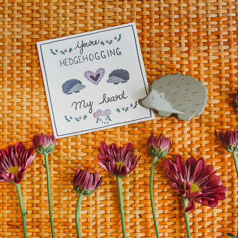 Flowers and a Tenderleaf Toys hedgehog next to a printable Valentine's Day card.