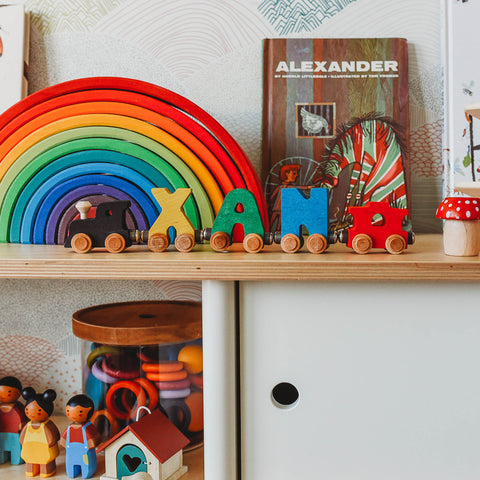 Maple Landmark Train and Grimm's wooden rainbow on a toy shelf.