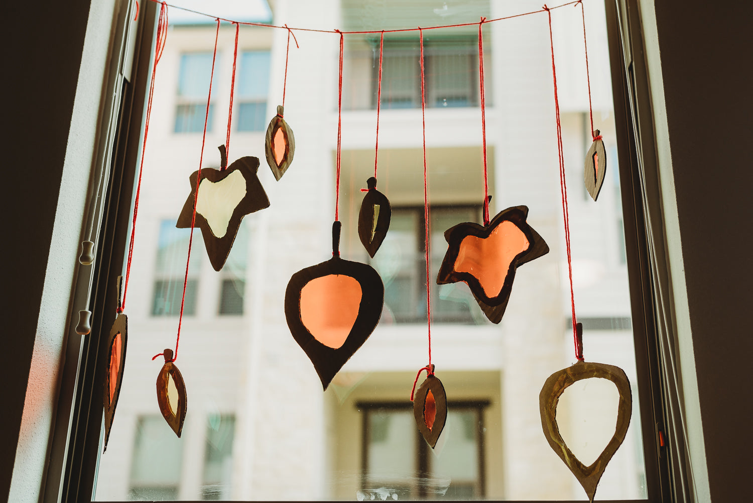 Series of cardboard leaves hanging from red yarn in a window.