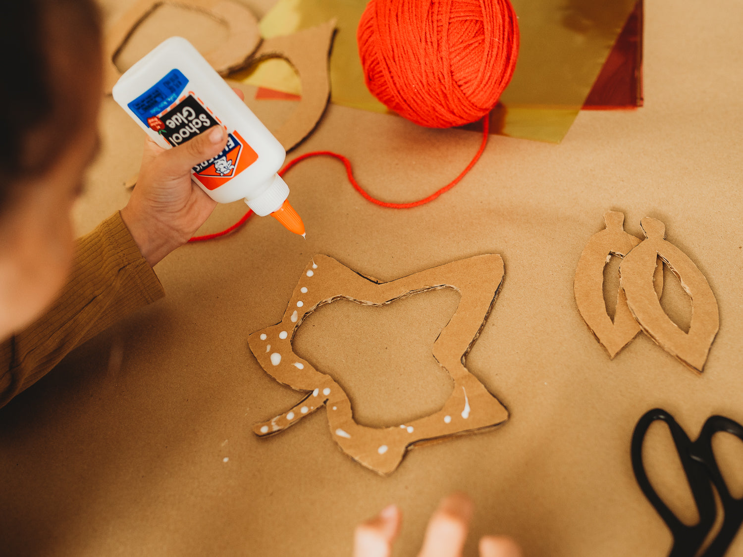 A child puts glue on cardboard for an eco-friendly fall crafts project