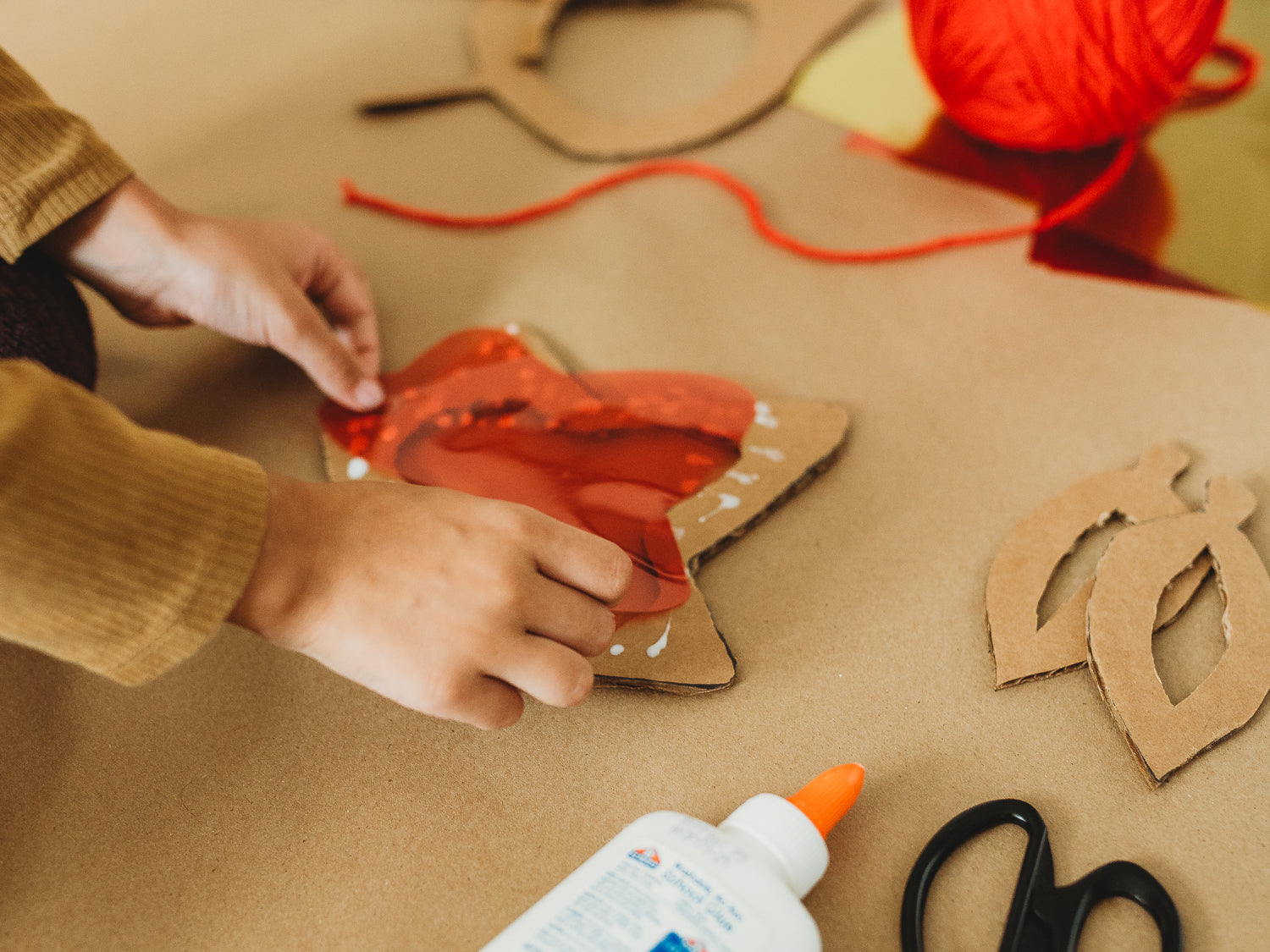 A child glues biodegradable red cellophane to cardboard for an eco-friendly fall craft project.