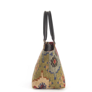Side view of Kilim Handbag Wine Green with black leather handles