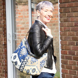 Women holding the Navy Kilim Hobo Bag with brown leather strap