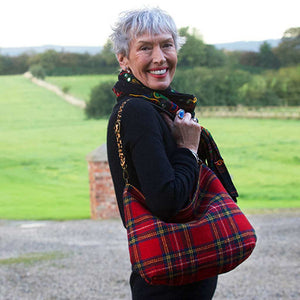 Woman holding the Red Tartan Harris Tweed Hobo Bag with Leopard Strap