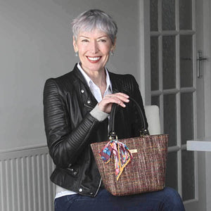 Woman holding the Pink Tweed Handbag with black leather handles and Twilly Scarf, by Umpie Bags