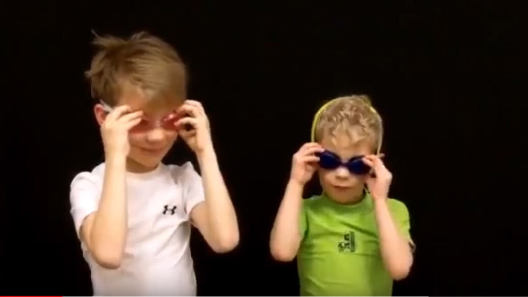 Two boys trying swim goggles in swimsuits
