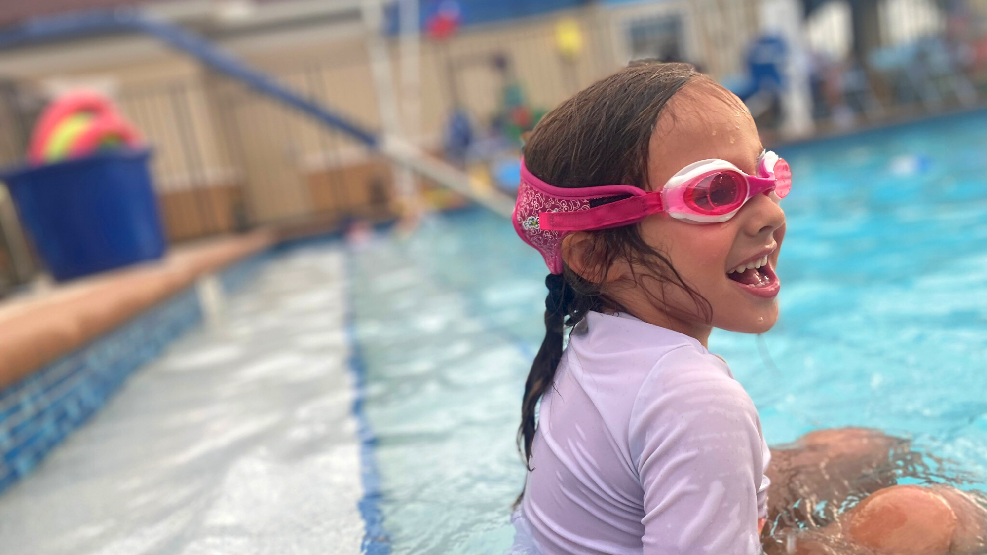 Young girl swimming at swim lessons wearing pink Frogglez swim goggles. Laughing, happy girl wearing swimming goggles in the pool. Pink neoprene strap with velcro adjusts easily.