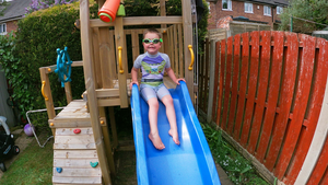 Cute boy wearing Frogglez on backyard slide into pool