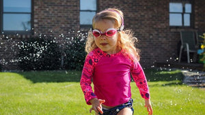 Little girl wearing Frogglez swim goggles with blue swim diaper and pink rash guard