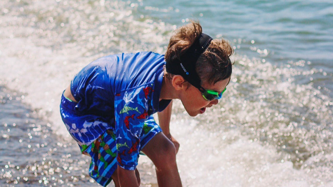 Boy in blue swimsuit with Frogglez goggles on plays on the beach on a sunny day. kids swim goggles. froggles. best kids swim goggles. beach. swim. goggles. swimming goggles. most comfortable swim goggles
