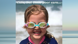 Girl at beach with sand filled goggles pulling ears