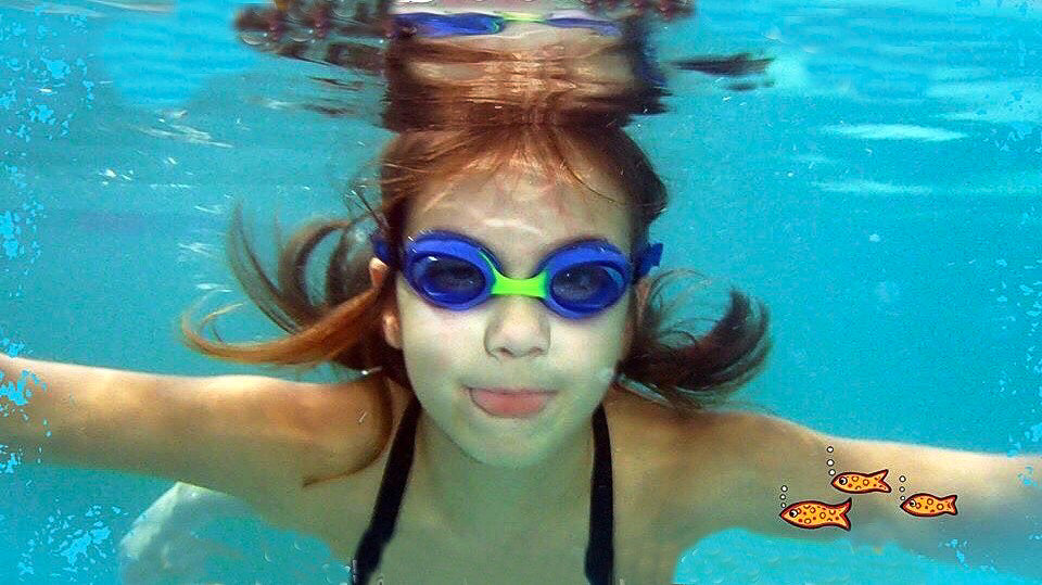 girl swimming underwater with blue Frogglez swim goggles