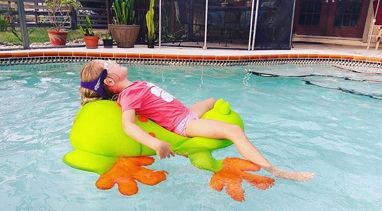 Girl swimmer in backyard swimming pool floating on a frog in a pink rashguard wearing Frogglez swim goggles. Frogglez goggles have a sturdy headband strap that is easy to use. Adjust easily with velcro.
