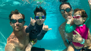 Family swimming underwater in pool wearing Frogglez swim goggles. Adult swim goggles and kids swim goggles for the whole family. Comfortable swimming goggles for curly hair. Toddlers and children swimming lessons in backyard pool.