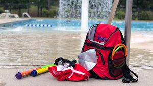 Frogglez swim goggles and swimming toys on red swim bag by swimming pool