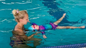 Young girl in mermaid swimsuit and Frogglez swim goggles taking swim lessons from blonde female instructor