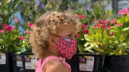 cute girl with curly hair wearing Frogglez pink cloth face mask with frog print. In front of flowers outside in the sunshine. Comfortable contoured face mask made just for kids.