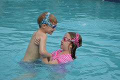 Two kids swimming in pool wearing Frogglez goggles