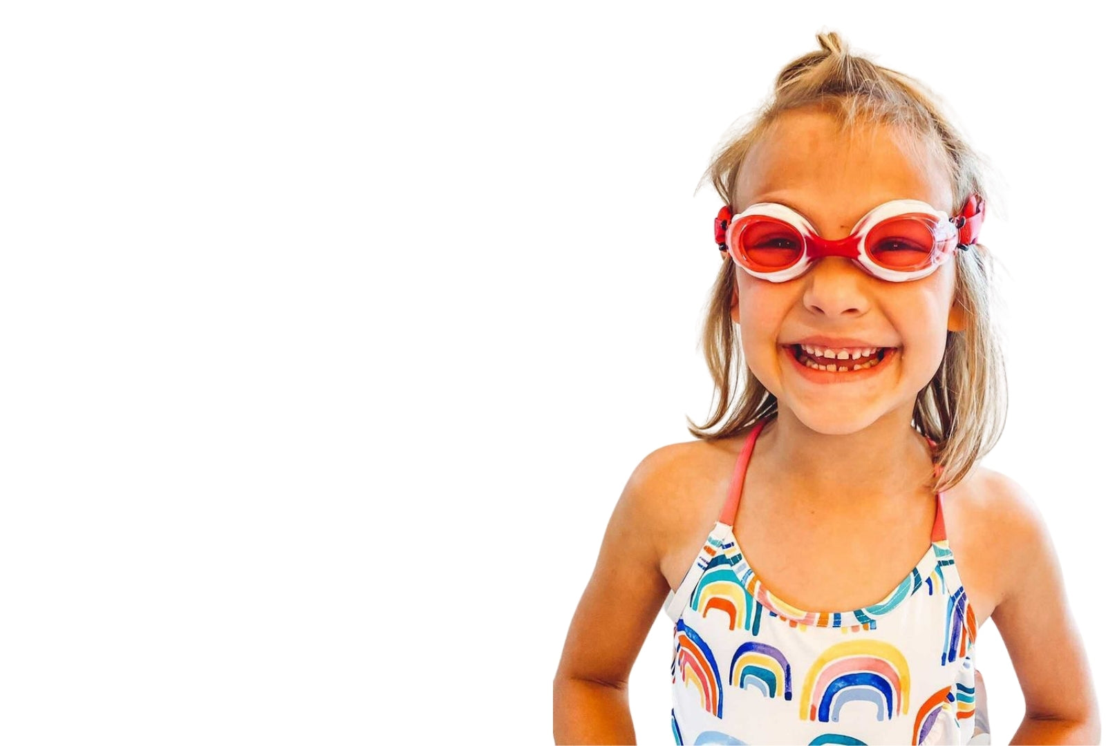 Smiling girl with light hair wearing Frogglez swim goggles wearing swimsuit