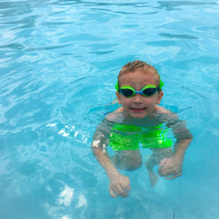 boy swimming in pool wearing Frogglez goggles