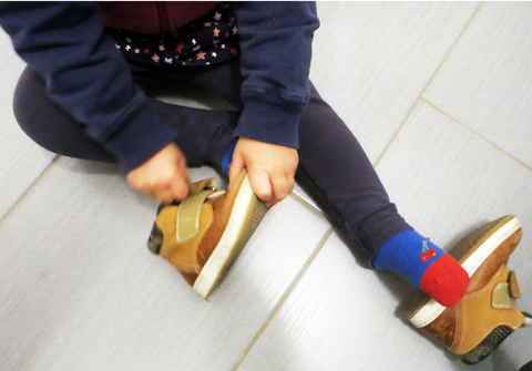 Child putting on shoe montessori method