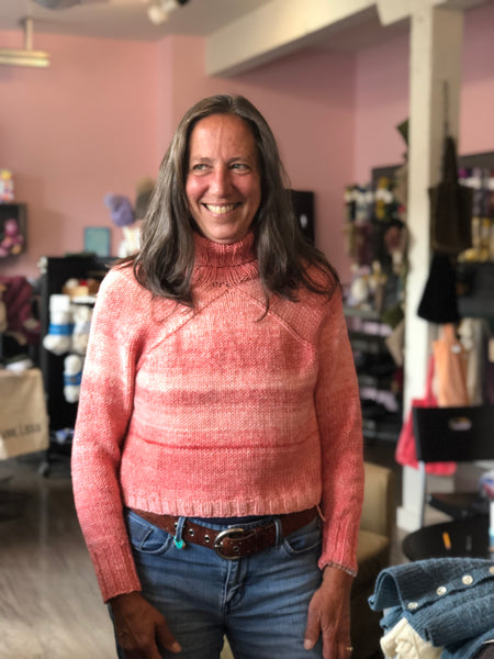 white woman wearing a turtle-neck pink sweater